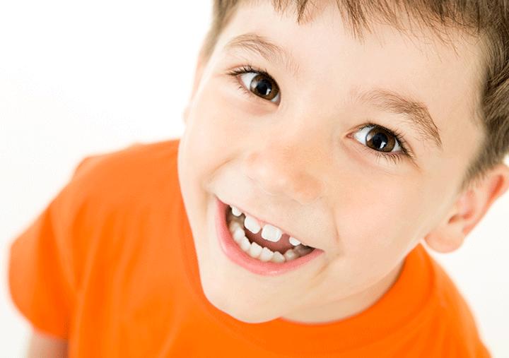 child smiling exhibiting teeth gaps